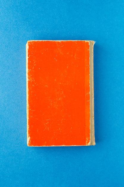 明るい青色の背景に古い赤い本。 Premium写真