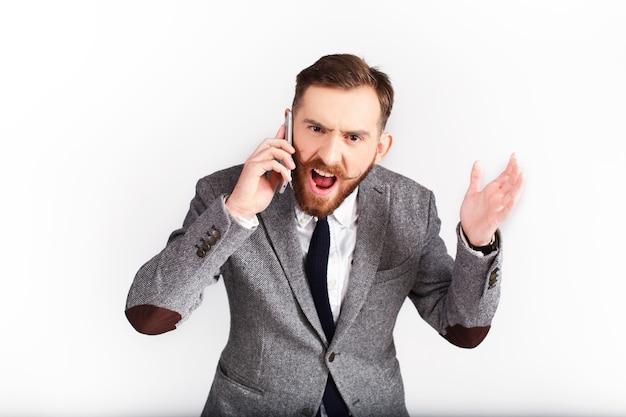 Сердитый мужчина в сером костюме разговаривает по телефону Бесплатные Фотографии