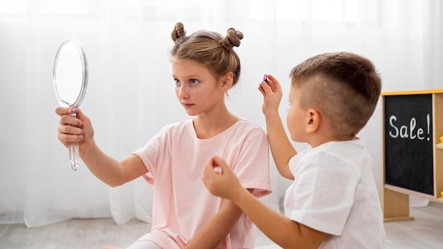Bambini non binari che giocano insieme in un salone di bellezza Foto Gratuite