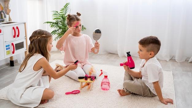 Bambini non binari che giocano a un gioco di salone di bellezza Foto Gratuite