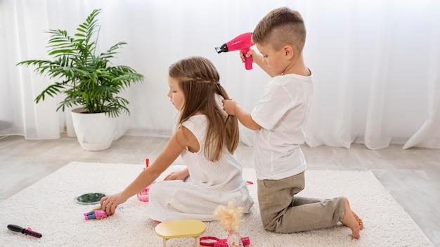 Bambini non binari che giocano insieme un gioco di salone di bellezza Foto Gratuite