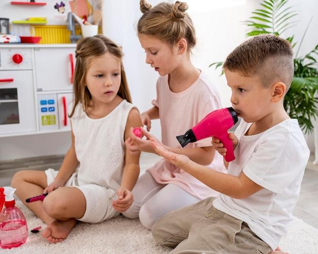 Bambini non binari che giocano insieme a un gioco di salone di bellezza Foto Gratuite