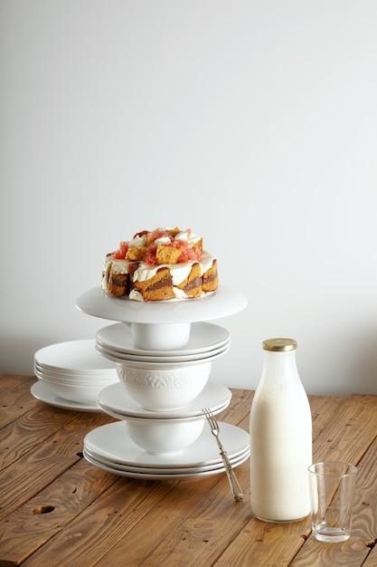 Torta nuziale non tradizionale con crema, cioccolato e pompelmo in equilibrio su piramide di tazze e piattini bianchi con accanto una bottiglia di latte Foto Gratuite