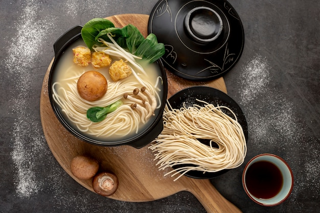 Noodle bowls on a wooden plate on a grey background Free Photo