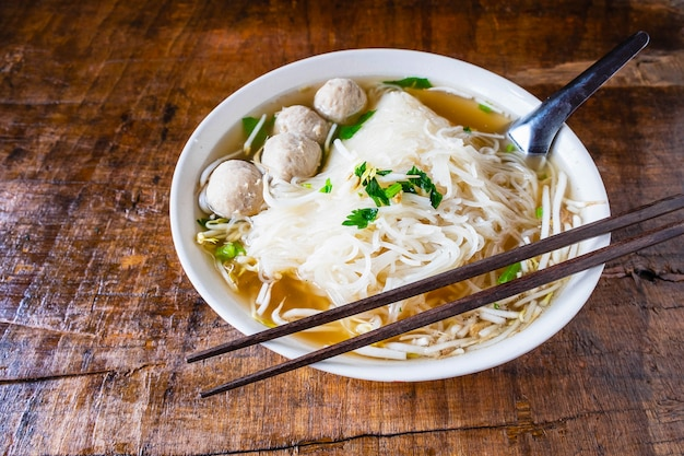 Noodle and meatballs in a bowl on a wooden table Premium Photo