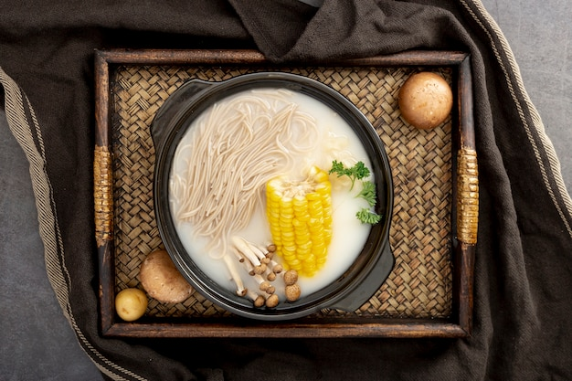 Noodle soup with corn in a black bowl on a wooden table Free Photo