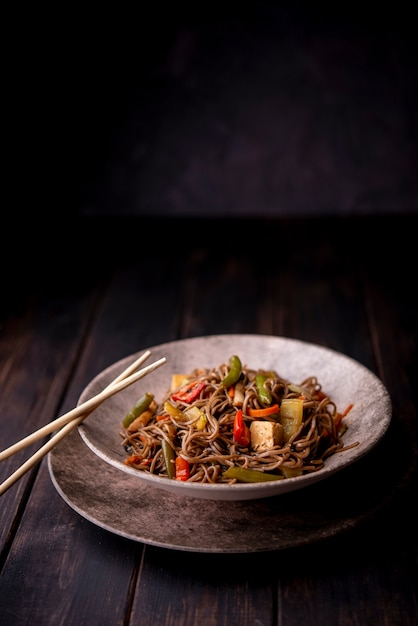 Noodles in bowl with chopsticks and copy space Premium Photo