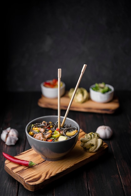 Noodles in bowl with chopsticks and garlic Free Photo