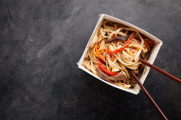 Noodles in a box with vegetables and beef. Premium Photo