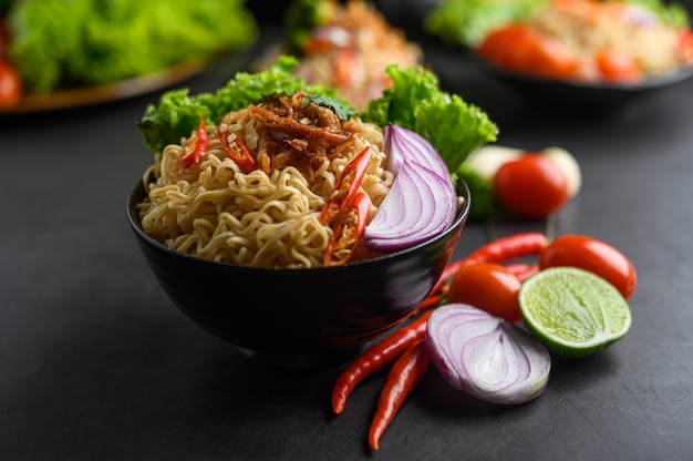 Noodles spicy in the bowl with ingredients on black cement surface Free Photo