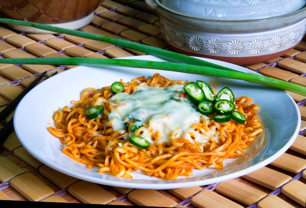 Noodles spicy sauce korean style on top melted cheese decorated with slice green chili and scallion put on white plate Premium Photo