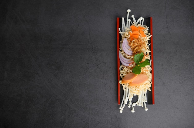 Noodles spicy in wooden tray with ingredients on black cement surface. Free Photo