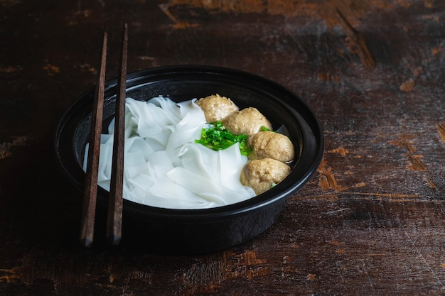 Noodles with meatballs on a wooden table Premium Photo