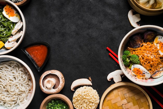 Noodles with sauce and vegetables on black background Free Photo