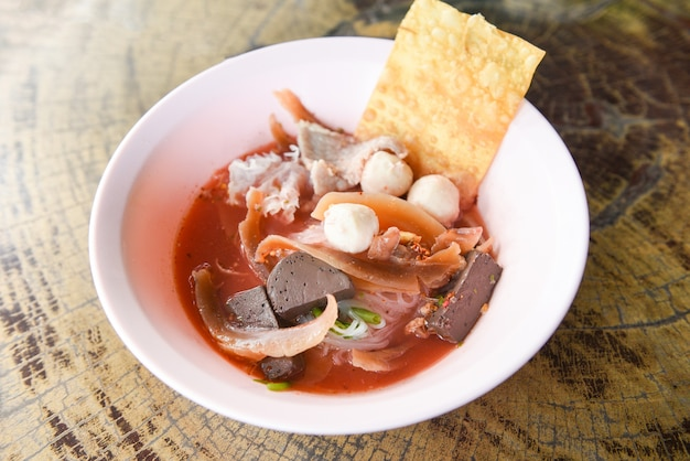 Лапша с морепродуктами на красном супе - острая и острая тайская лапша с лапшой, кальмаром, свининой, рыбным шариком Premium Фотографии