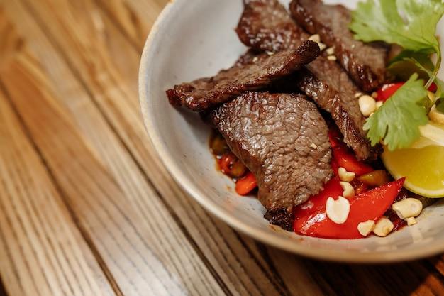 Лапша с телятиной и овощами на сером столе. Premium Фотографии