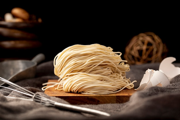 Tagliatelle su un piatto di legno su uno sfondo nero Foto Gratuite