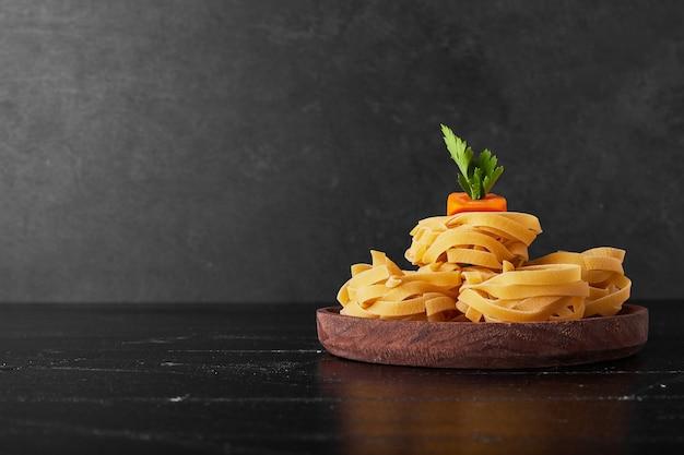 Tagliatelle su un piatto di legno con verdure Foto Gratuite