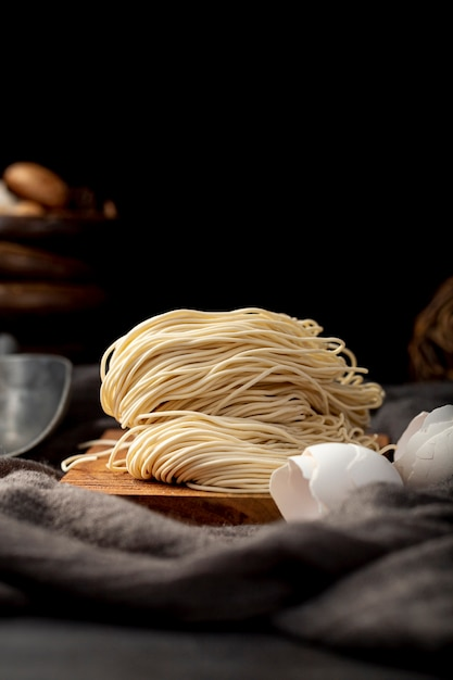 Noodles on a wooden support on a black background Free Photo