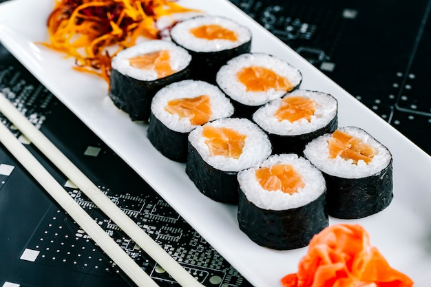 Nori sushi rolls with salmon served with ginger wasabi and shredded carrot Free Photo