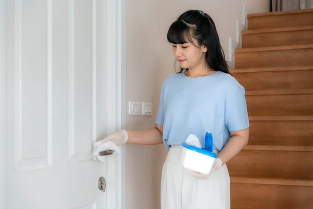 Normal shot of a asian woman disinfecting the door knobs by disinfectant disposable wipes from box.