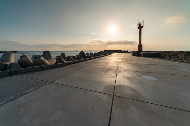 North pier with breakwaters, sunset seascape. modern lighthouse in sunlight. Premium Photo