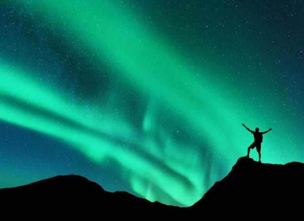 오로라와 노르웨이에서 산의 정상에 팔을 제기 서있는 남자의 실루엣. 오로라 보리 얼리 스와 행복한 사람. 프리미엄 사진