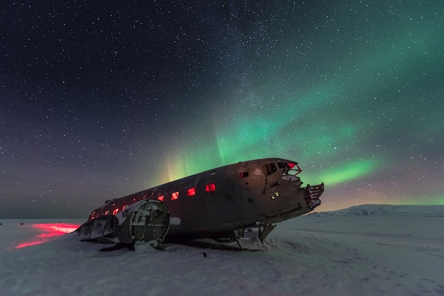 Northern lights aurora borealis over plane wreckage in iceland Premium Photo
