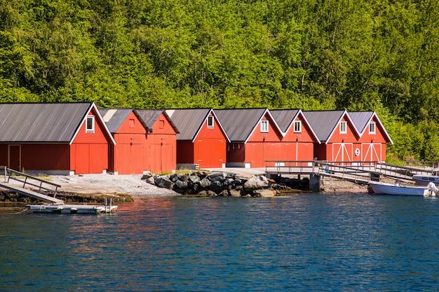 Норвежский пейзажный вид фьорда с красными домами и рыбацкими лодками в норвегии. Premium Фотографии
