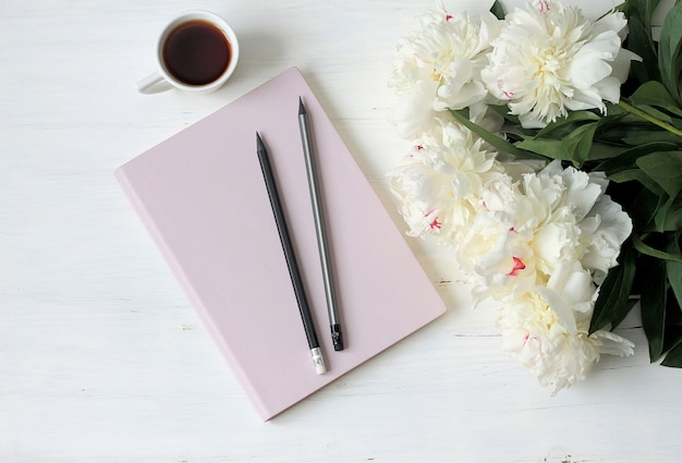 Note book, peonies and cup of coffee on light wood Premium Photo