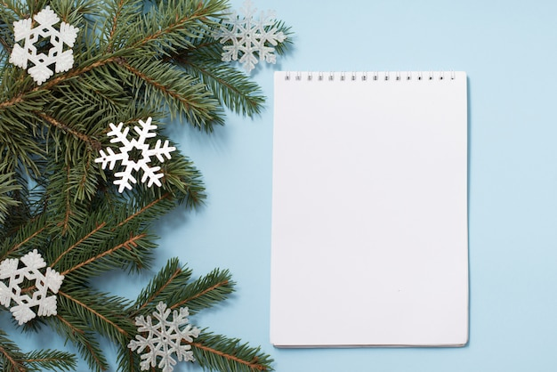 Note book with wish list. snowy fir branches on blue , copycopyspace. christmas and winter concept. Premium Photo