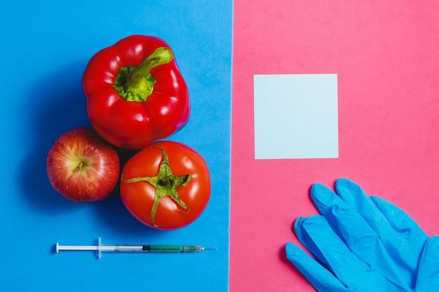 Note, green liquid in syringe, red tomato, apple, pepper, blue gloves. Premium Photo