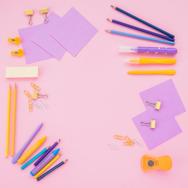 Note papers; color pencils and paper clips over pink backdrop Free Photo
