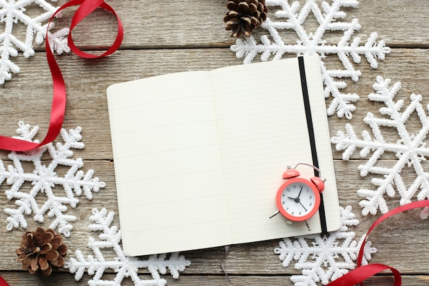 Notebook and alarm clock on snowflakes Free Photo