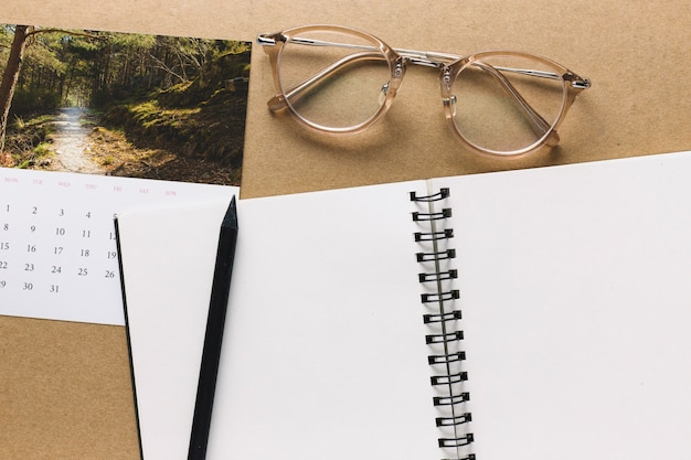 Notebook and glasses near calendar Free Photo