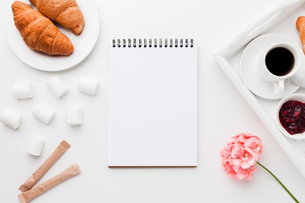 Notebook beside tray with cup of coffee and croissant Free Photo