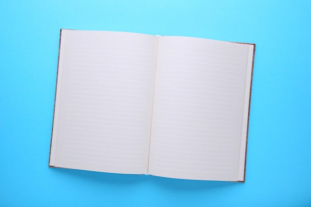Notebook on a blue background, close up Premium Photo