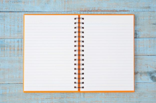 Notebook on blue wood table Free Photo