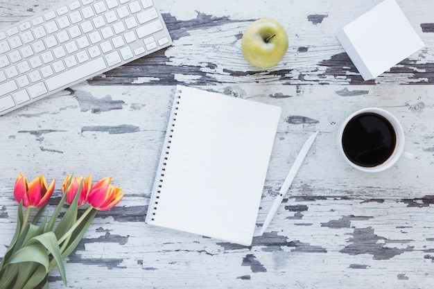 Notebook and coffee cup near keyboard and tulip flower on grungy desk Free Photo