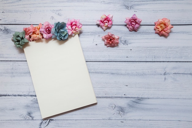 Notebook decorated with multicolored flowers on a wooden background. view from above. concept for march 8 and spring. Premium Photo