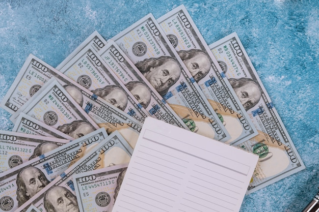 Notebook and dollars on blue background. Premium Photo