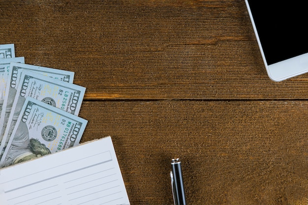 Notebook and dollars smart phone on wood Premium Photo