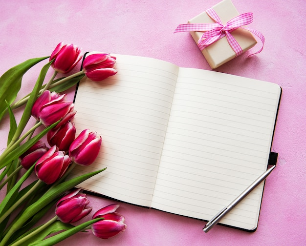 Notebook, gift box and pink tulips Premium Photo