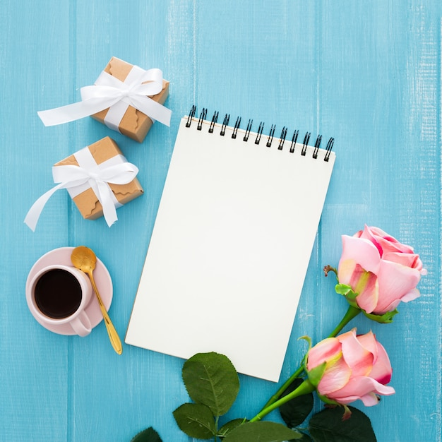 Notebook, gift boxes, coffee, and pink roses on a blue wooden Free Photo