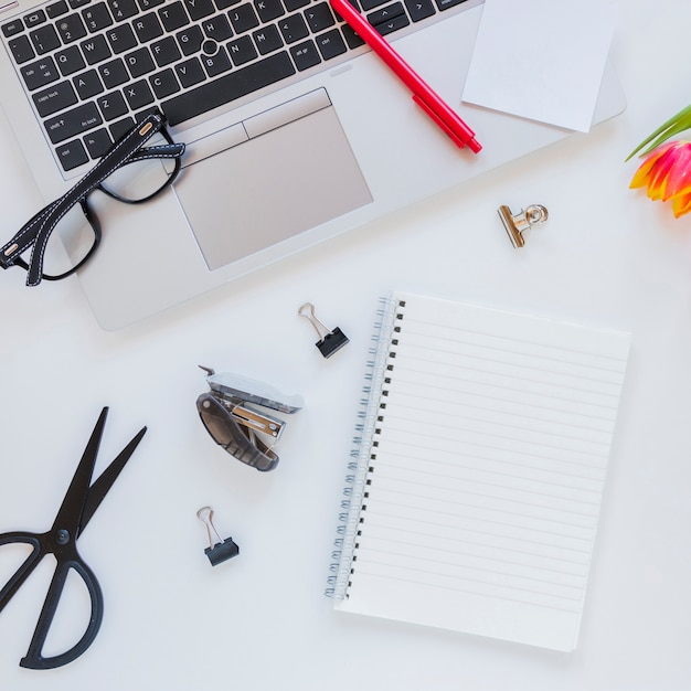 Notebook and laptop near stationery on white desk Free Photo