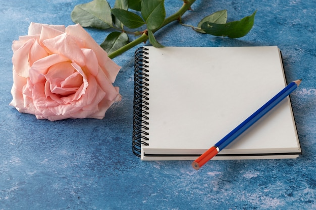 A notebook mock up with a rose Premium Photo