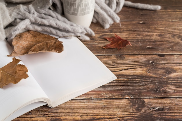 Notebook near autumn leaves and scarf on table Free Photo
