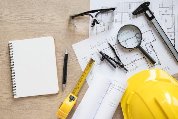 Notebook near blueprints and construction supplies Premium Photo