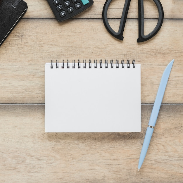 Notebook near calculator and scissors on table Free Photo
