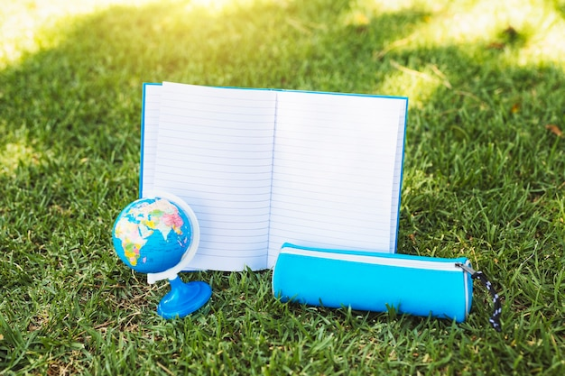 Notebook near pencil case and globe on grass Free Photo